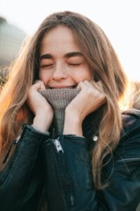 A woman grinning into her turtle neck