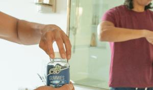 A man opening up a bottle of CBD men's gummies