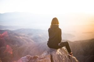 A woman sitting on an edge of a cliff